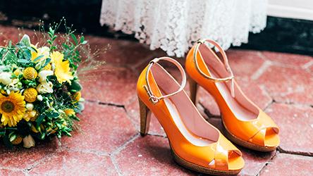 Une paire d'escarpins de mariée est posée à coté du bouquet de mariage