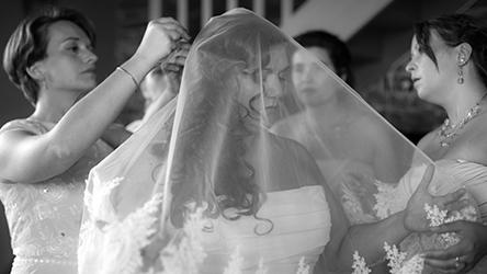 Une mariée se fait aider de sa wedding planner lors de la mise en place de son voile