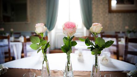 Trois soliflores contenant trois roses ornent la table d'honneur des mariés